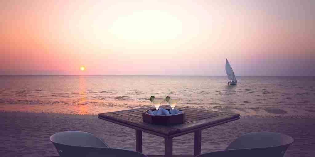 Azura Benguerra sundowners on table on beach with dhow.jpg