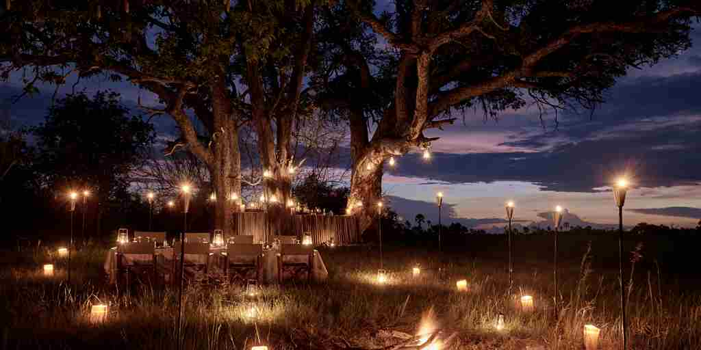 sanctuary baines camp dining night botswana yellow zebra safaris